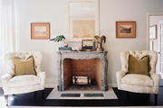 A pair of tufted armchairs flanking a mantel topped with a brass ram head