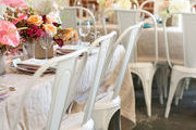 A set of neutral tablescapes with colorful flowers and white chairs.