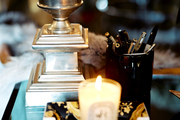 A hurricane lamp, office supplies, and a candle on a desk