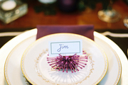 A purple napkin and china setting on a dining table decorated for the holidays