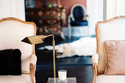 A pair of white chairs flanking a modern side table and a brass lamp