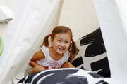 Poppy Edwards in a tepee with outdoor pillows on her rooftop patio