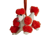 A poodle ornament cheerfully groomed in bright red
