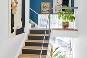 Blue accent wall staircase with houseplants and art.