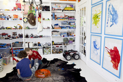 A playroom lined with shelves and framed kids' art
