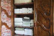 An armoire used for storing linens with custom upholstered panels