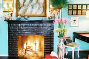 A painted-brick fireplace and a geometric rug in a blue-walled living space