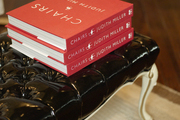 A stack of books on a black tufted ottoman