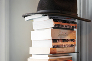 A stack of books topped by a hat