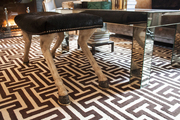 A whimsical stool with hoof legs next to a mirrored coffee table