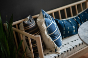 Detail of bench seat with blue grasscloth pillows.
