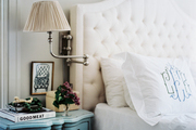 A white tufted headboard with monogrammed pillow shams
