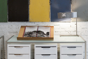 """A vintage locker collection and a modern lamp by Ted Harris on CB2 console and file cabinets against walls painted in Benjamin Moore """"Chantilly Lace"""""""