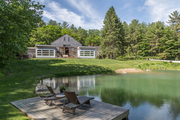 The view of a rustic barn from beyond the pond.