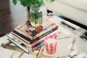 Books and a vase of branches on a glass coffee table