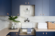 Blue cabinets with leather pulls in laundry room.