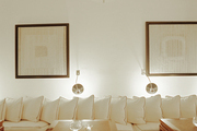 Square tables pulled up to a banquette covered with white pillows