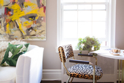Animal print chairs and large scale art in sitting area.