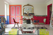 A rose-pink radiator, a gilded mirror, and pendant lamps in a Paris dining room
