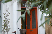 A tomato-red door announces the bold color choices within.
