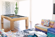 A living room with brightly colored couches, a black and white printed rug and a pool table.