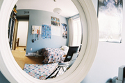 A convex mirror in a boy's bedroom in shades of blue