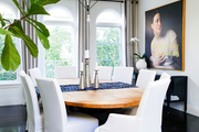 A formal dining room with an interesting light fixture and art.