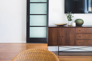 Brown wicker chair and a brown wood credenza in a white living room.