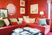 A room with red walls filled with a red sectional and a black coffee table