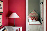 A deep red hallway leading to a guest bedroom