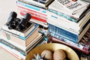 Stacks of books and a bowl of decorative accessories beside a white chair