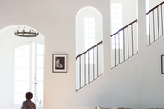 Arched windows along a staircase with iron banister