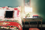 A mix of floral patterns in a green bedroom