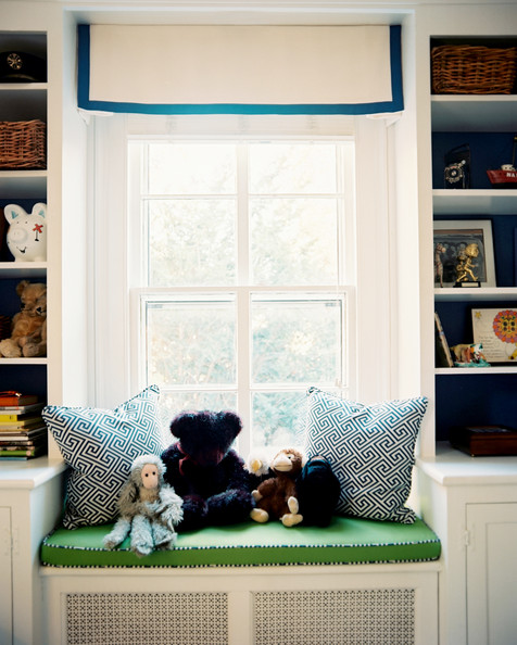 Kids' Room - A window seat with a roman shade between white built-in bookcases