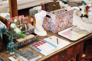 A weathered wooden table topped with colorful desk accessories and trays