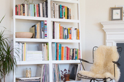 A pair of white bookshelves with a wireframe chair.