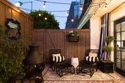 Outdoor lounge chairs atop area rug on outdoor patio.