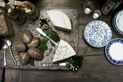 Cheese and bread platter atop wooden serving tray.
