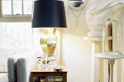A brass lamp with a black lampshade beside a white bust on a pedestal