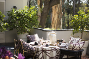 An outdoor dining table surrounded by chairs
