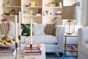Large built-in shelving behind white sofa and low marble table.