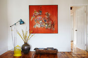 Abstract orange painting with yellow and brown decor pieces.