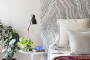 An abstract painted gray wall behind a bed.