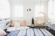 A white and blue kids room with a swing.