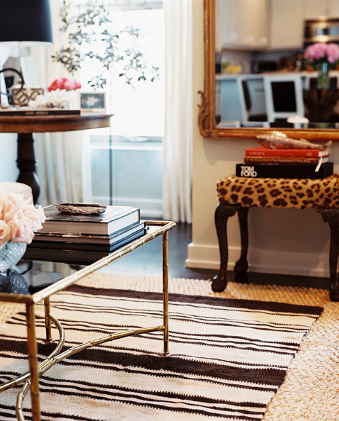 Layered Rugs - A gold faux-bamboo coffee table atop layered rugs