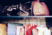 Clutches and handbags on blue shelves backed by wallpaper