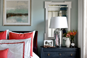 A mirror opens up the space behind this decorated bedside table.