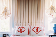 A pompom-fringed canopy above monogrammed bed linens