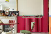 A pink-painted radiator and gilded mirror in a Paris dining room