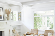 A room with white walls and beach furniture pieces.
